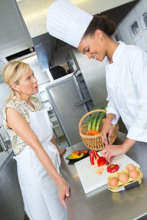 Dois cozinheiros chefe fêmeas na cozinha gastronômico fotografia de stock royalty free