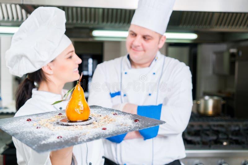 Dois cozinheiros chefe famosos que guardam sua sobremesa deliciosa Trabalham na fotografia de stock