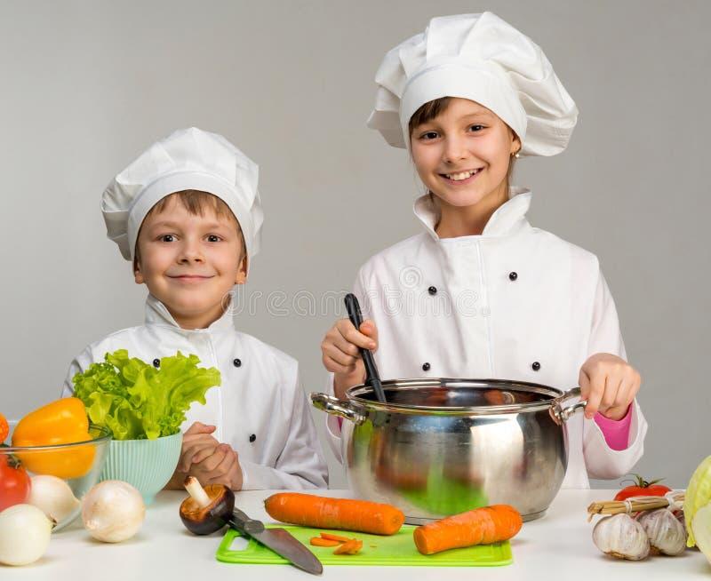 Dois cozinheiros chefe pequenos cozinheiro e sorriso foto de stock