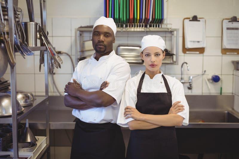 Dois cozinheiros chefe que estão com braços cruzaram-se na cozinha comercial imagens de stock