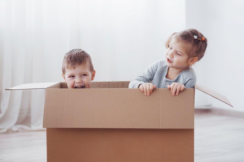 Dois crianças menino e menina apenas moveram-se em uma casa nova Foto do conceito As crianças têm o divertimento foto de stock