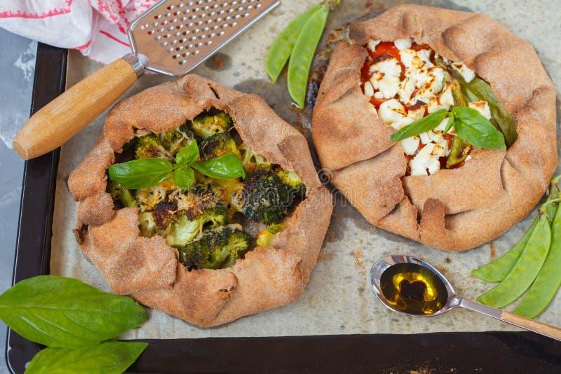 Dois crostatas ou Galette do vegetariano com brócolis, tomates, che imagens de stock royalty free