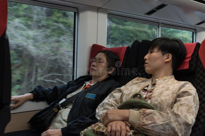 Dois da mulher asiática das senhoras sentam-se no trem, um sono, um throug do olhar imagens de stock