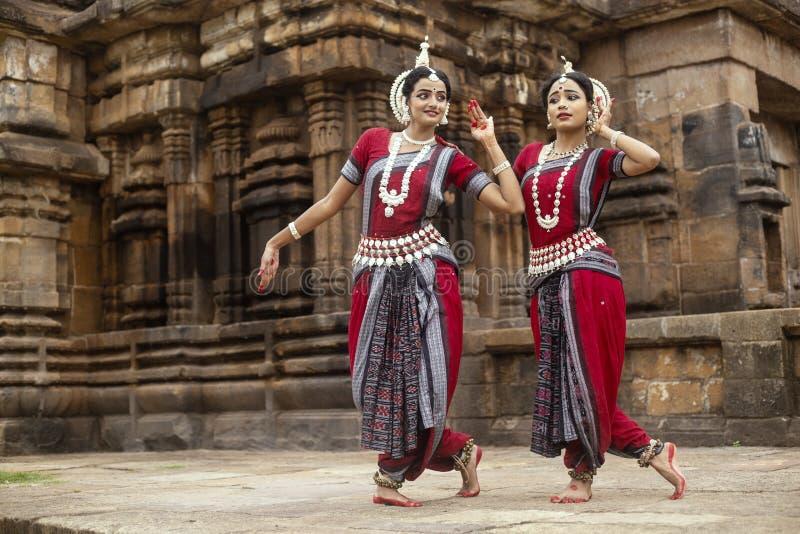 Dois dançarinos clássicos indianos do odissi que golpeiam uma pose na frente do templo de Mukteshvara, Bhubaneswar, Odisha, Índia fotografia de stock royalty free