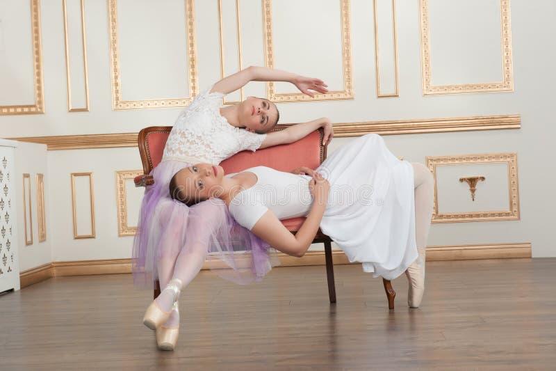 Dois dançarinos de bailado bonitos novos que sentam-se no sofá foto de stock