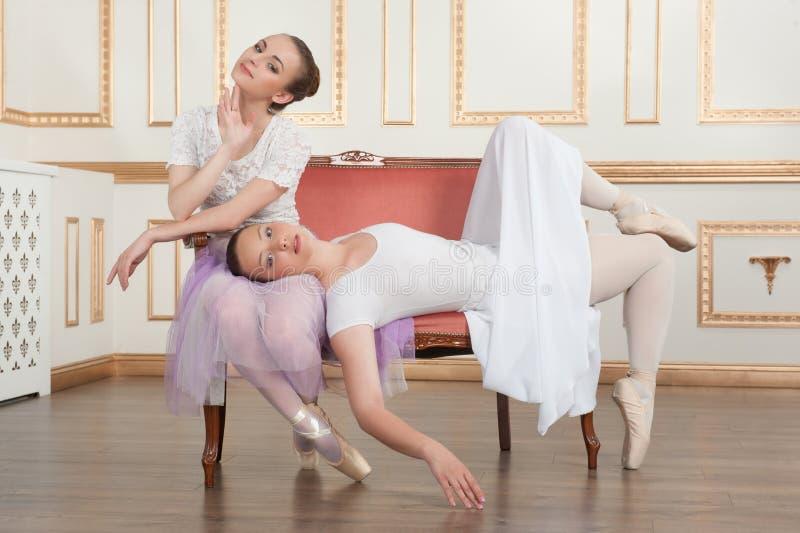 Dois dançarinos de bailado bonitos novos que sentam-se no sofá foto de stock royalty free