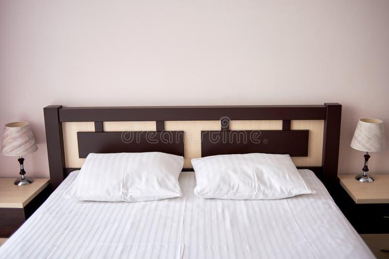 Dois descansos macios brancos na cama com a cabeceira de madeira no interior do quarto do hotel, espaço da cópia Lâmpada clássica fotografia de stock royalty free