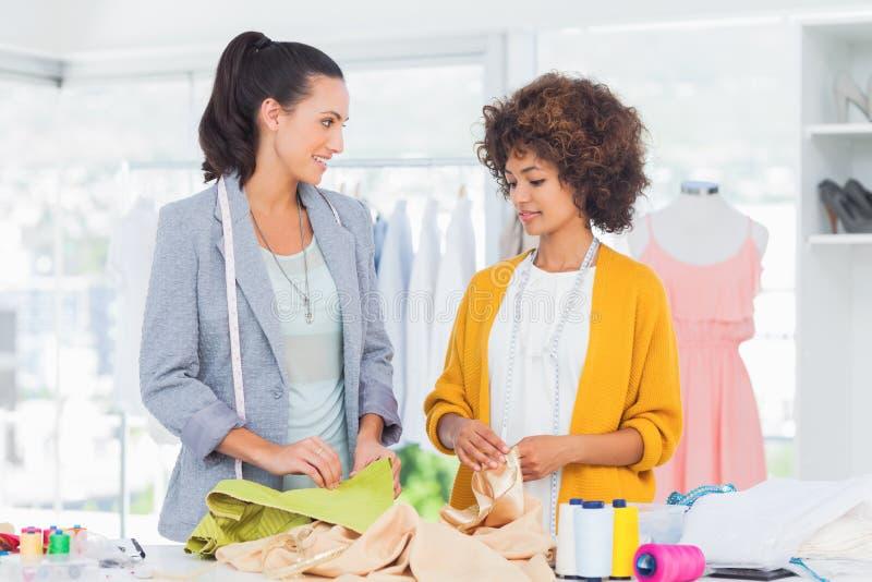 Dois desenhadores de moda alegres que tocam na matéria têxtil foto de stock royalty free