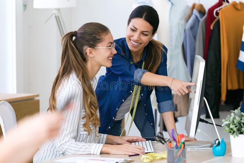 Dois desenhadores de moda novos que falam e que trabalham com o computador na oficina costurando fotografia de stock royalty free