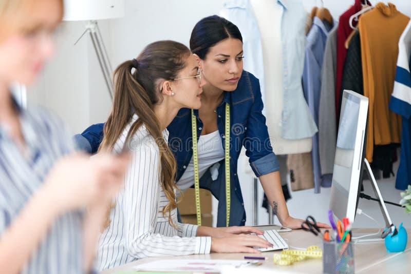 Dois desenhadores de moda novos que falam e que trabalham com o computador na oficina costurando imagens de stock