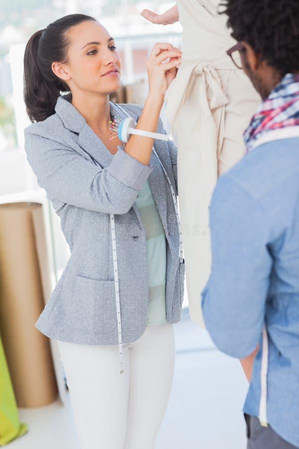 Dois desenhadores de moda que ajustam o vestido imagens de stock