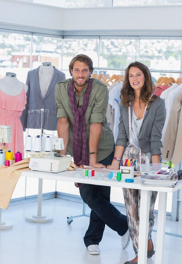 Dois desenhadores de moda que estão em um escritório criativo brilhante imagens de stock royalty free