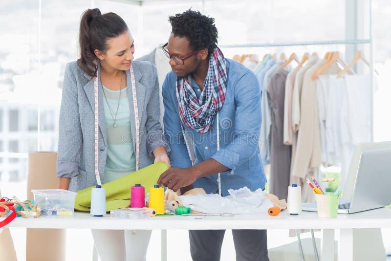 Dois desenhadores de moda que trabalham junto no escritório fotos de stock royalty free