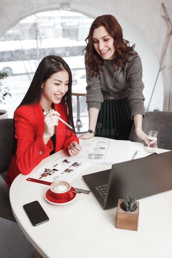 Dois desenhistas das meninas estão trabalhando com portátil e documentação no projeto no escritório à moda Criação do projeto fotografia de stock royalty free