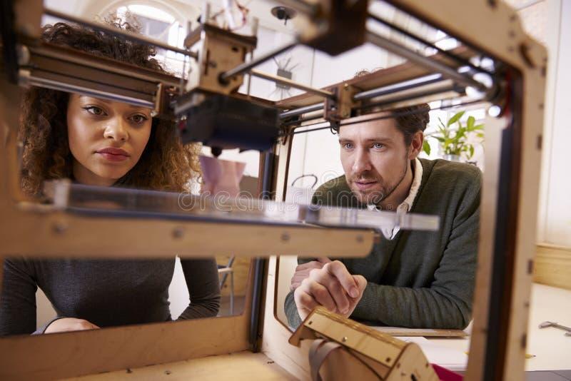 Dois desenhistas que trabalham com 3D a impressora In Design Studio fotos de stock royalty free