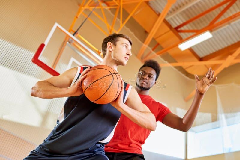 Dois desportistas que jogam o basquetebol imagens de stock
