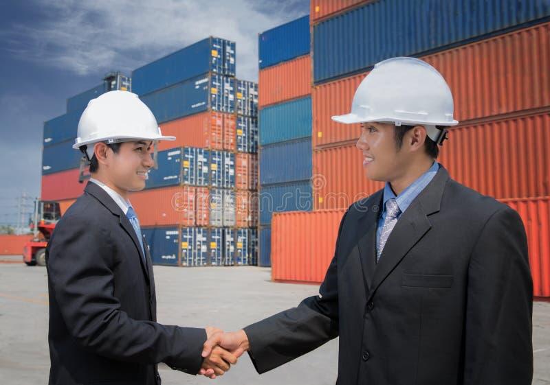Dois do homem de negócios adulto meados de que agita as mãos aproximam o recipiente de carga imagem de stock royalty free