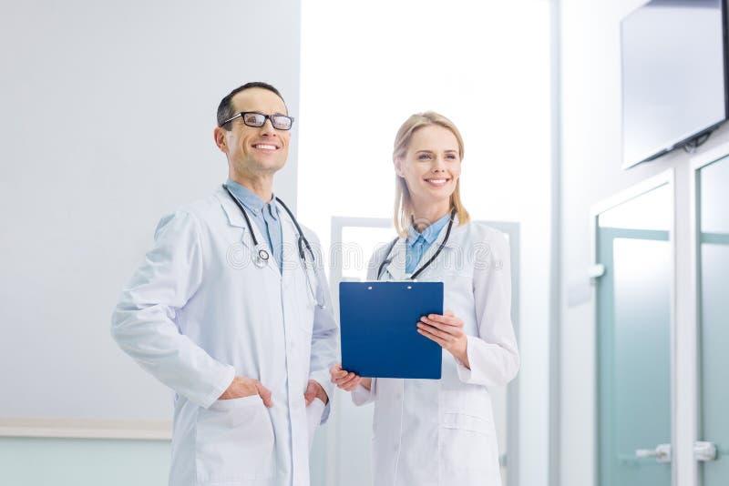 dois doutores alegres nos revestimentos brancos com estetoscópios e posição do diagnóstico foto de stock