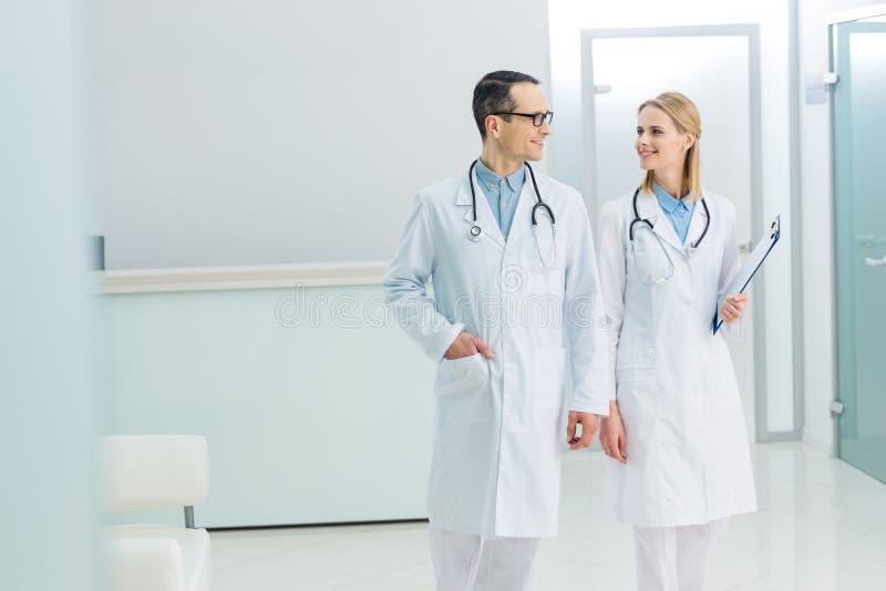 dois doutores de sorriso nos revestimentos brancos com estetoscópios e diagnóstico fotos de stock