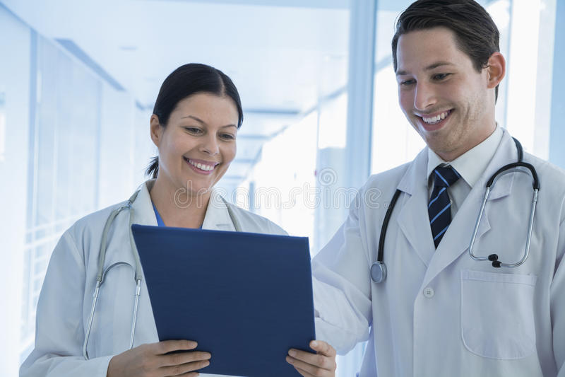 Dois doutores de sorriso que examinam para baixo um informe médico no hospital fotos de stock