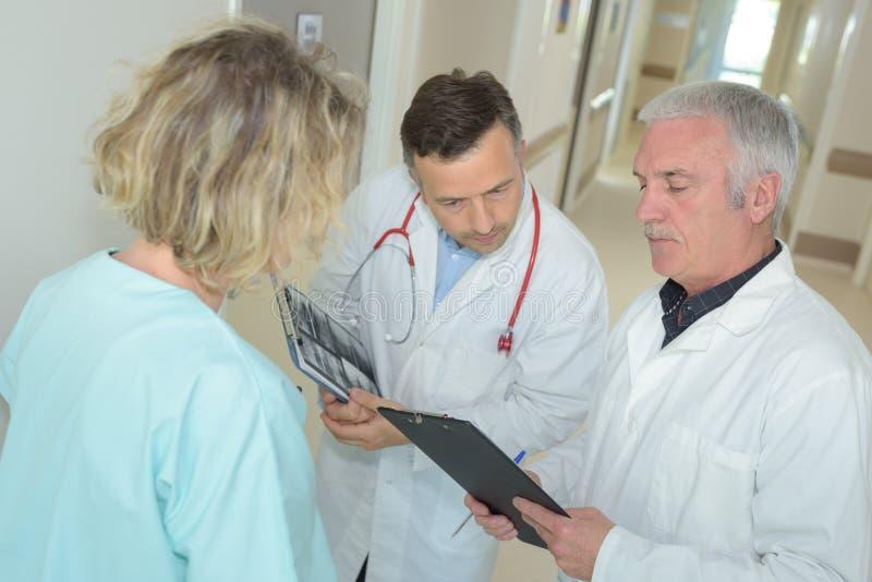 Dois doutores e enfermeira que olham a prancheta no hospital imagem de stock royalty free