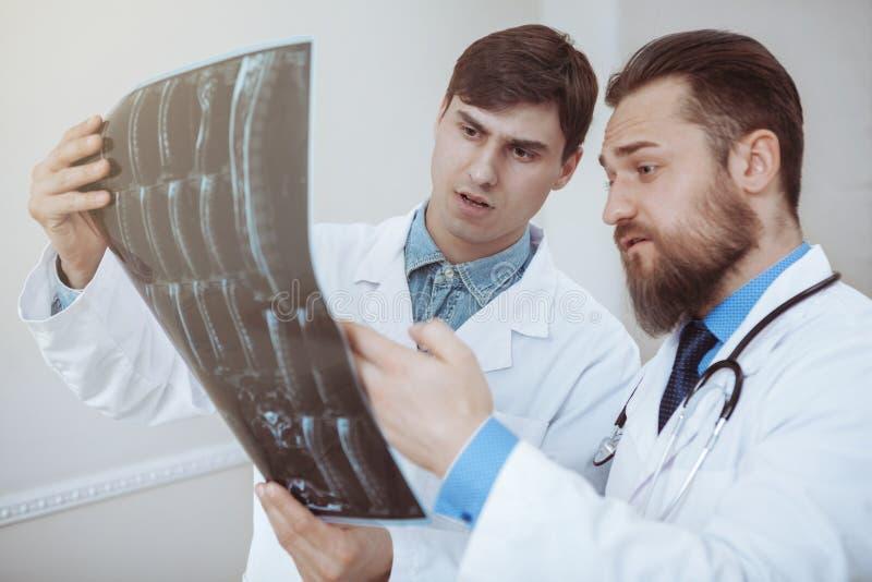 Dois doutores masculinos que discutem varreduras do raio X no hospital foto de stock royalty free