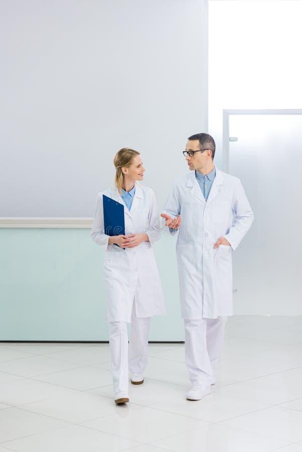 dois doutores nos revestimentos brancos com fala do diagnóstico foto de stock