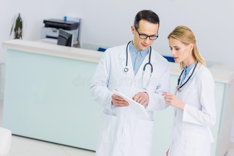 dois doutores nos revestimentos brancos com tabuleta que discutem o diagnóstico imagens de stock royalty free