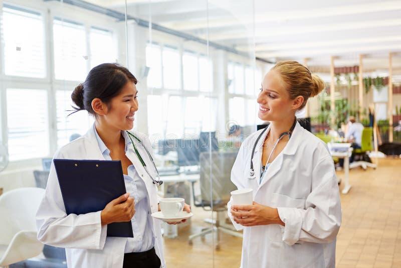 Dois doutores novos em sua ruptura de café fotografia de stock