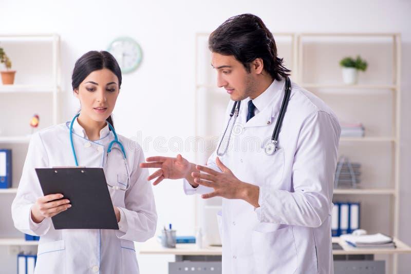 Dois doutores novos que trabalham na cl?nica fotos de stock
