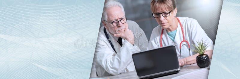 Dois doutores que discutem sobre o relatório médico no portátil; bandeira panorâmico fotografia de stock royalty free