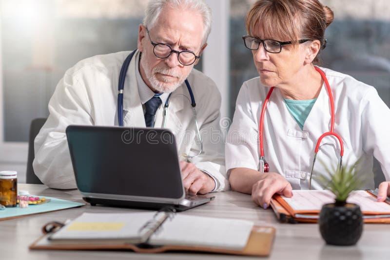 Dois doutores que discutem sobre o relat?rio m?dico no port?til imagens de stock royalty free