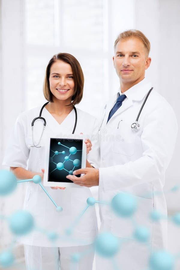 Dois doutores que mostram o PC da tabuleta com moléculas fotografia de stock royalty free