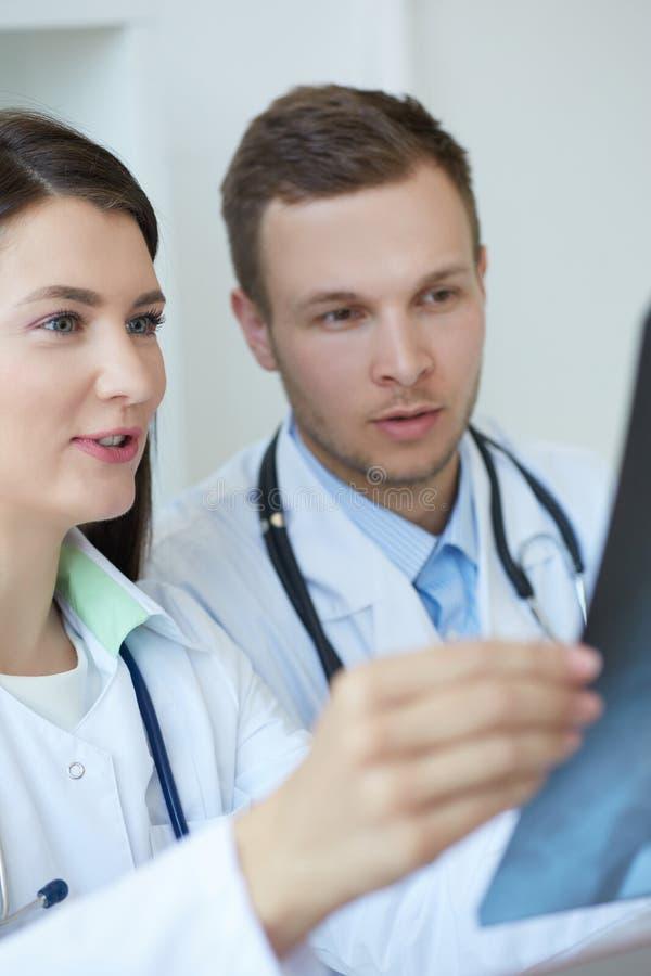 Dois doutores seguros sérios que discutem o raio X de seu paciente e que fazem um diagnóstico Radiologista ou foto de stock