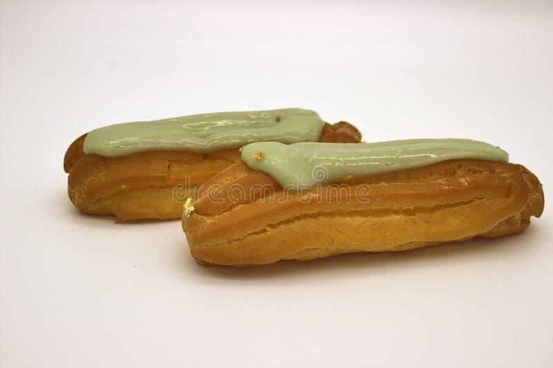 Dois Eclairs deliciosos do pistache Uma imagem isolada no fundo branco foto de stock