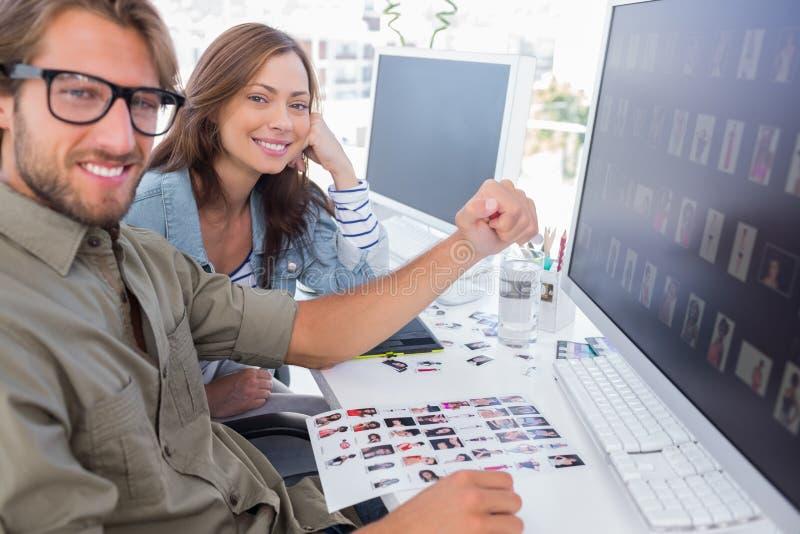 Dois editores de fotos de sorriso que trabalham com folhas do contato imagem de stock