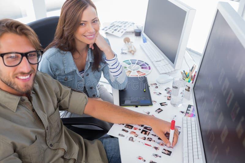 Dois editores de fotos felizes que trabalham com folhas do contato imagens de stock