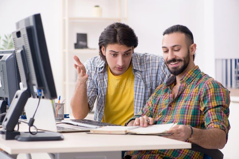 Dois ele especialistas que trabalham no escrit?rio imagens de stock