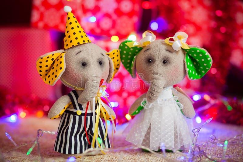 Dois elefantes do brinquedo do presente estão em um fundo de luzes e de caixas de Natal foto de stock royalty free