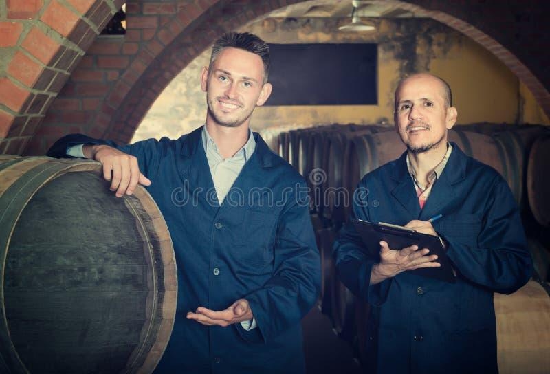 Dois empregados de sorriso da adega dos homens que escrevem a nota imagem de stock royalty free