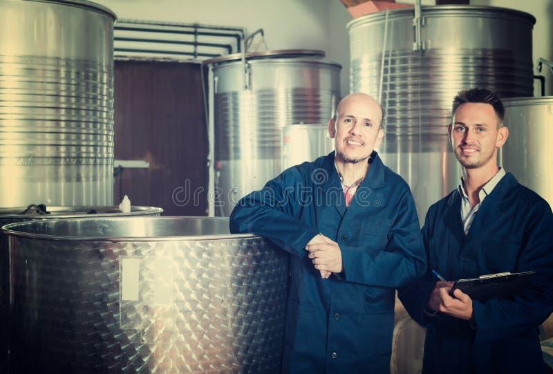 Dois empregados do sexo masculino na adega fotografia de stock royalty free