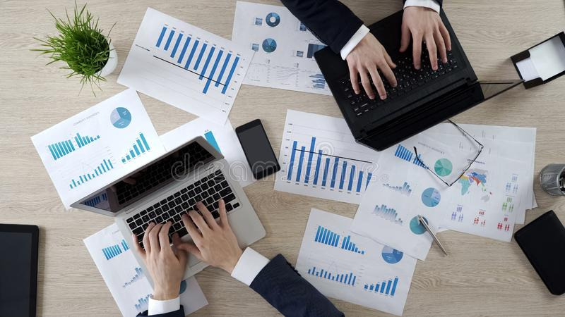 Dois empregados incorporados que datilografam nos portáteis, trabalhando no projeto do negócio, vista superior foto de stock