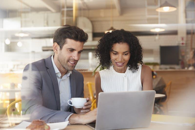 Dois empresários encontram-se na cafetaria disparada através da janela fotos de stock royalty free
