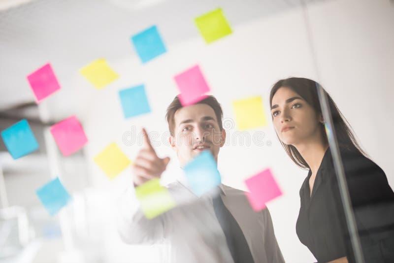 Dois empresários que discutem e que planeiam o conceito Parte dianteira do marcador e das etiquetas da parede de vidro Escritório foto de stock royalty free
