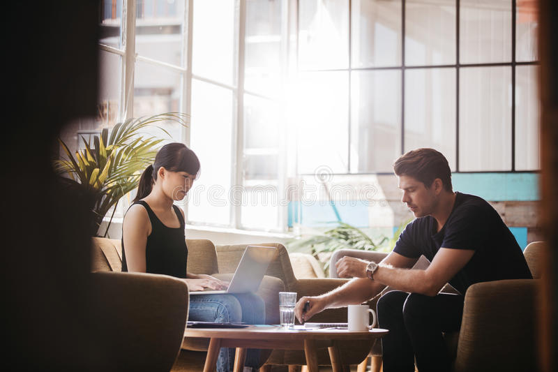 Dois empresários que encontram-se na área da entrada do escritório moderno fotografia de stock royalty free