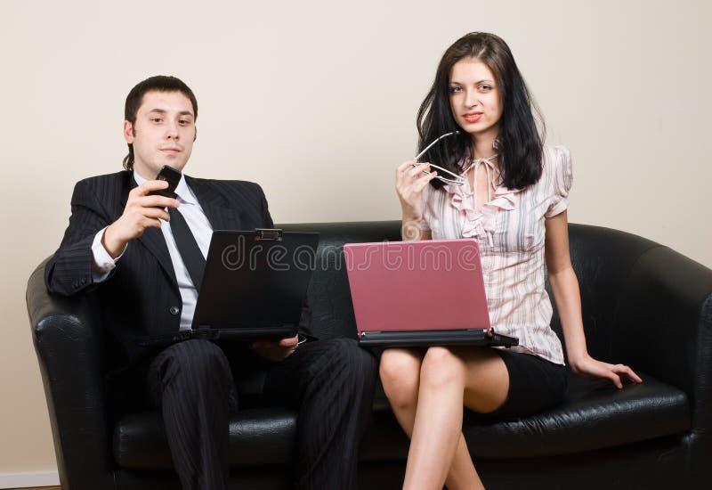 Dois empresários que usam os portáteis, sentando-se no sofá imagens de stock
