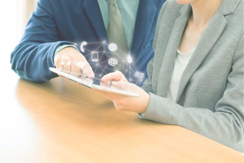 Dois empresários seguros que usam uma tabuleta digital junto ao trabalhar foto de stock