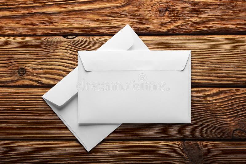 Dois envelopes brancos com letras no fundo escuro de madeira velho Placas para o desenhista Conceitos, ideias para serviços posta foto de stock royalty free