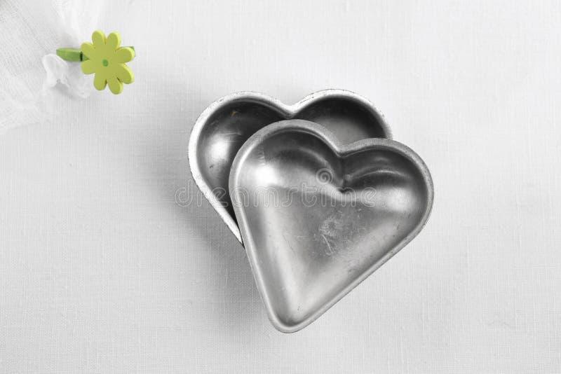 Dois estanhos do bolo do coração, utensílio romance da cozinha foto de stock royalty free