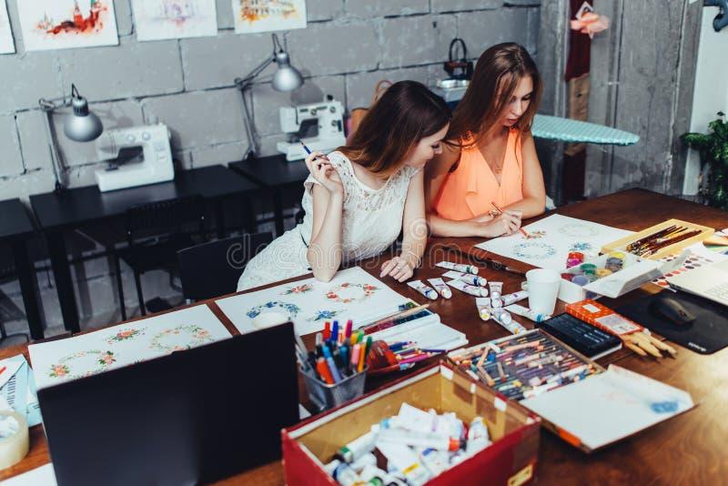 Dois estudantes adultos fêmeas que tiram imagens com os pastéis que sentam-se na mesa coberta com os materiais da pintura durante imagens de stock royalty free